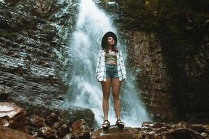 kvinna i brun hatt som njuter av utsikten över vattenfallet foto