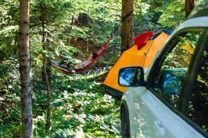 kvinna som ligger i hängmattstältet och bilen på bakgrunden foto