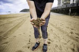 händer som kastar sand på stranden foto