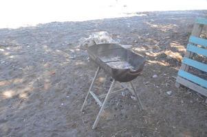 metallpanna för matlagning av kött står på sanden foto