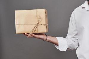 mans händer ger paket inslaget i brunt papper och bundna med grov garn foto