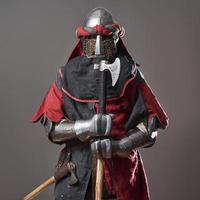 medeltida riddare på grå bakgrund. porträtt av brutal smutsig ansikte krigare med kedjepost rustning röda och svarta kläder och stridsyxa foto