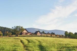 byhus på kullar med gröna ängar sommardag. hus av herdar i berg i karpater foto