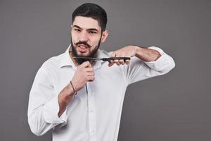 inte mer skägg. porträtt av stilig ung man som skär sitt skägg med sax och tittar på kameran medan han står mot grå bakgrund. ny trend foto