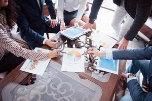 affärsteams brainstorming. marknadsföringsplan undersöker. pappersarbete på bordet, bärbar dator och mobiltelefon foto