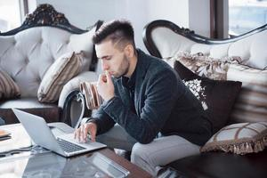 ung affärsman som arbetar på moderna loftkontor. man som bär vit skjorta och använder modern laptop. panoramafönster bakgrund foto
