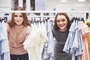 unga vackra kvinnor på den veckovisa tygmarknaden - bästa vänner som delar fritid med att ha roligt och shoppa i gamla stan på en solig dag - flickvänner som njuter av vardagslivet foto