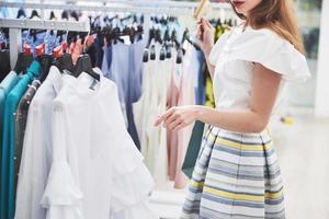 försäljning, mode, konsumentism och människor koncept - glad ung kvinna med shoppingkassar väljer kläder i köpcentret eller klädaffär foto