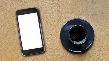 närbild skott av mockup blank skärm smartphone och kaffe mugg plats på gult betonggolv, ovanifrån skott. foto