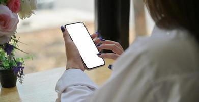 handen på en ung kvinna som använder en smartphone för att söka information på internet. foto