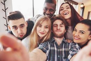 vänner som har kul på restaurang. två pojkar och fyra tjejer dricker att göra selfie, gör fredstecken och skrattar. på förgrunden kvinna som håller smart telefon. alla bär vardagskläder foto