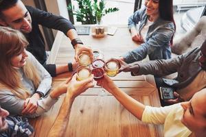 vy uppifrån. händer på människor med glas whisky eller vin, firar och skålar för att hedra bröllopet eller annat firande foto