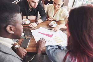 start diversitet lagarbete brainstorming möte koncept. företag team arbetskamrater dela världsekonomi rapport dokument laptop. människor arbetar planering starta. grupp unga hipsters diskutera café foto
