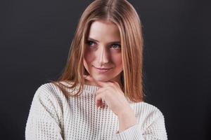 närbild porträtt av vacker ung kvinna i vit tröja och jeans, isolerad på svart bakgrund foto
