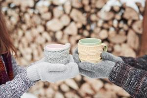par händer i vantar tar en mugg med varmt te i vinterparken foto