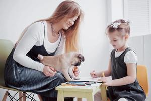mor och barn dotter drar är engagerade i kreativitet på dagis. liten mops med dem foto
