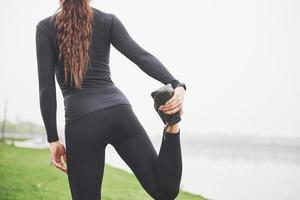 ung fitness kvinna löpare sträcker benen innan du kör på park foto
