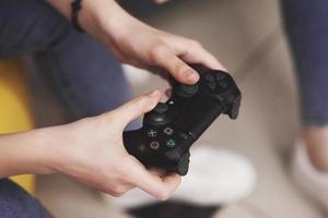 kvinnan leker på konsolen och håller joysticken i händerna foto