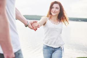 lyckligt ungt par som njuter av en ensam strandbackriding foto