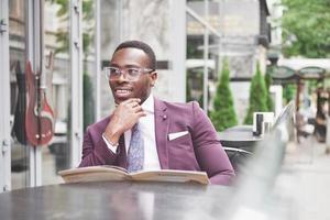 en vacker afroamerikansk affärsman läser en meny på ett café foto