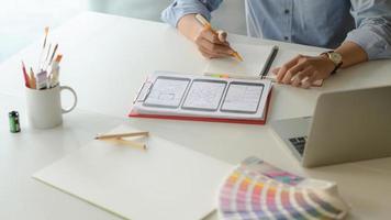 beskurna skott av ung designer som arbetar med smartphone -applikationsprojekt med surfplatta och anteckningsbok i modernt kontorsrum. foto
