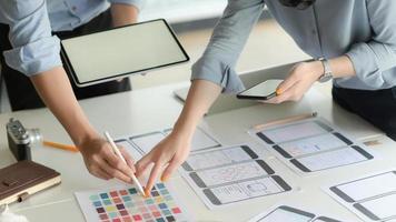 beskurna skott av unga ux designer team som arbetar med smartphone applikationsprojekt med hjälp av digital surfplatta i moderna kontorsrum. foto