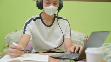 manlig student med mask som använder en bärbar dator och tar anteckningar för tentamen. han studerade hemma för att skydda covid-19. foto