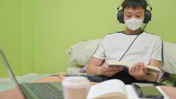 manlig student med mask som läser en bok på sängen för att förbereda sig för tentamen. han studerade hemma för att skydda covid-19. foto