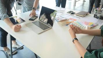 ux -teamet designar en applikation för smartphones med en bärbar dator på ett modernt kontor. foto