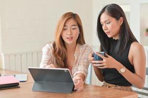 två asiatiska kvinnor som håller en kaffekopp och använder en bärbar dator diskuterar planer för hennes nästa projekt. foto