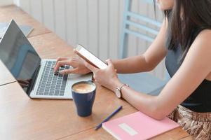 kvinna som håller en smartphone och använder en bärbar dator på ett bord med en kaffekopp på en modern arbetsplats. foto
