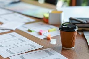 beskuren bild av en applikationsdesigners skrivbord med en mobil skärmskiss och ta bort kaffe på hemmakontoret. foto
