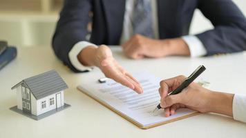 underteckna ett husköpskontrakt mellan husmäklaren och kunden. foto