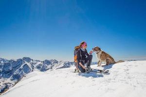 tjej skidtur med sin hund på toppen av berget foto