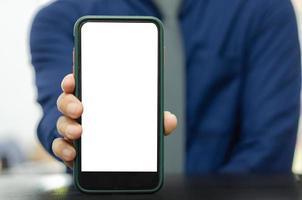 mocka en mobiltelefon i manens hand. tom skärm med text eller bild för en annons. foto