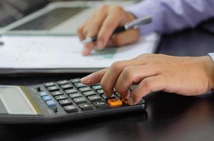 affärsman hand trycka på en miniräknare affär, finans, skatt och investeringar koncept. foto