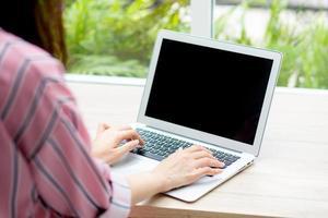 ung asiatisk kvinna som arbetar på bärbar dator. foto