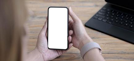 närbild kvinna handen använder en smart telefon med tom skärm på café kafé. foto