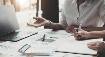 två affärskvinnor arbetar tillsammans för att brainstorma hur man växer företaget och planerar för att kontrollera företagets ekonomi i enlighet med planen. finansiella koncept. foto