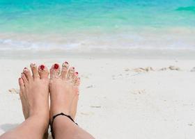 kvinnafötter och röda naglar på stranden foto