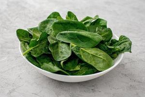 ren mat koncept. blad av färska ekologiska spenatgröna i en tallrik på en ljus bakgrund. hälsosam detox vår-sommar kost. vegansk rå mat. foto