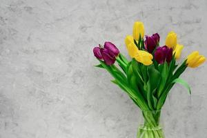 bukett lila och gula vårtulpanblommor i en glasvas på en ljus bakgrund. kopiera utrymme. mors dag. internationella kvinnodagen. foto
