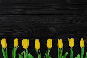 en rad med gula vårtulpanblommor på en svart träbakgrund. platt låg. kopiera utrymme. mors dag. internationella kvinnodagen. foto