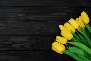 bukett med gula vårtulpanblommor på en svart träbakgrund. platt låg. kopiera utrymme. mors dag. internationella kvinnodagen. foto