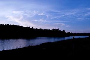 vackert himmellandskap med solnedgång över flodstranden foto