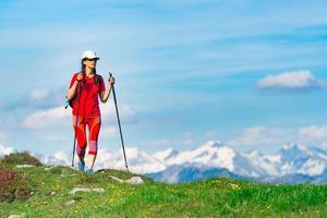 turistkvinna klädd i rött med höga berg med snö foto