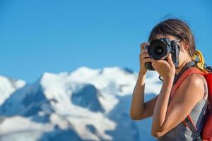 flicka som fotograferar i höga berg foto