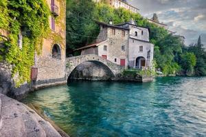 gammal liten by med en vacker stenbro längs Comosjön foto