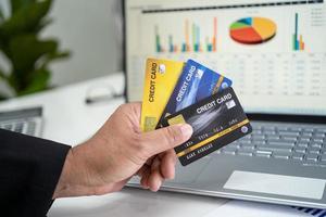 asiatisk revisor som arbetar, beräknar och analyserar rapportprojektbokföring med anteckningsbok och kreditkort i modernt kontor, ekonomi och affärsidé. foto