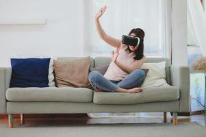upphetsad asiatisk kvinna i vr-headset som lyfter båda händerna upp foto